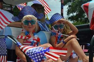 Girls dressed for July 4th on golf car
